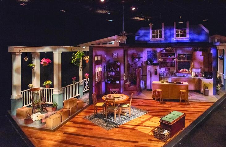 A theatre set of a house, including a living room, kitchen and front porch.
