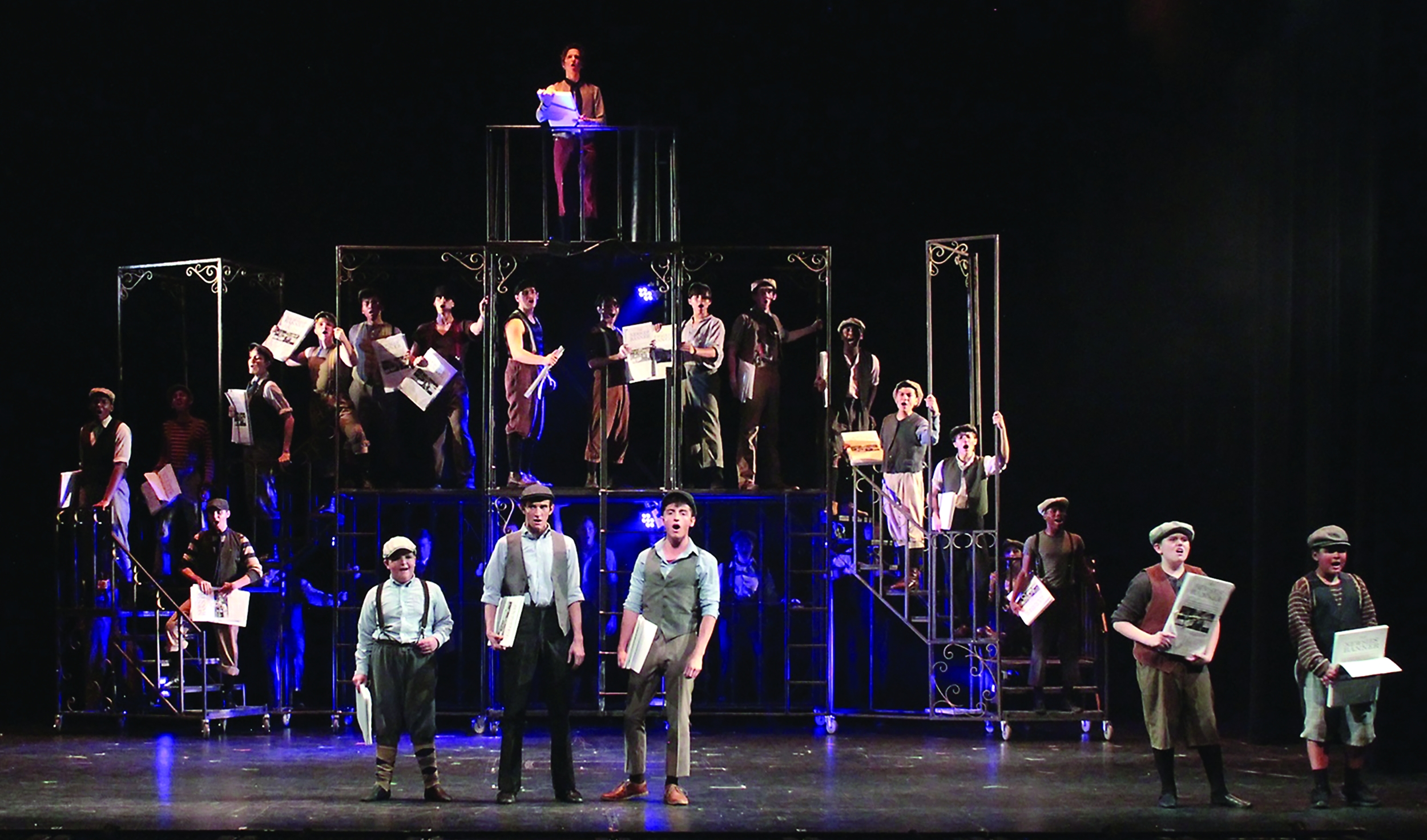 """Actors on stage sing in unison during a production of the """"Newsies."""""""