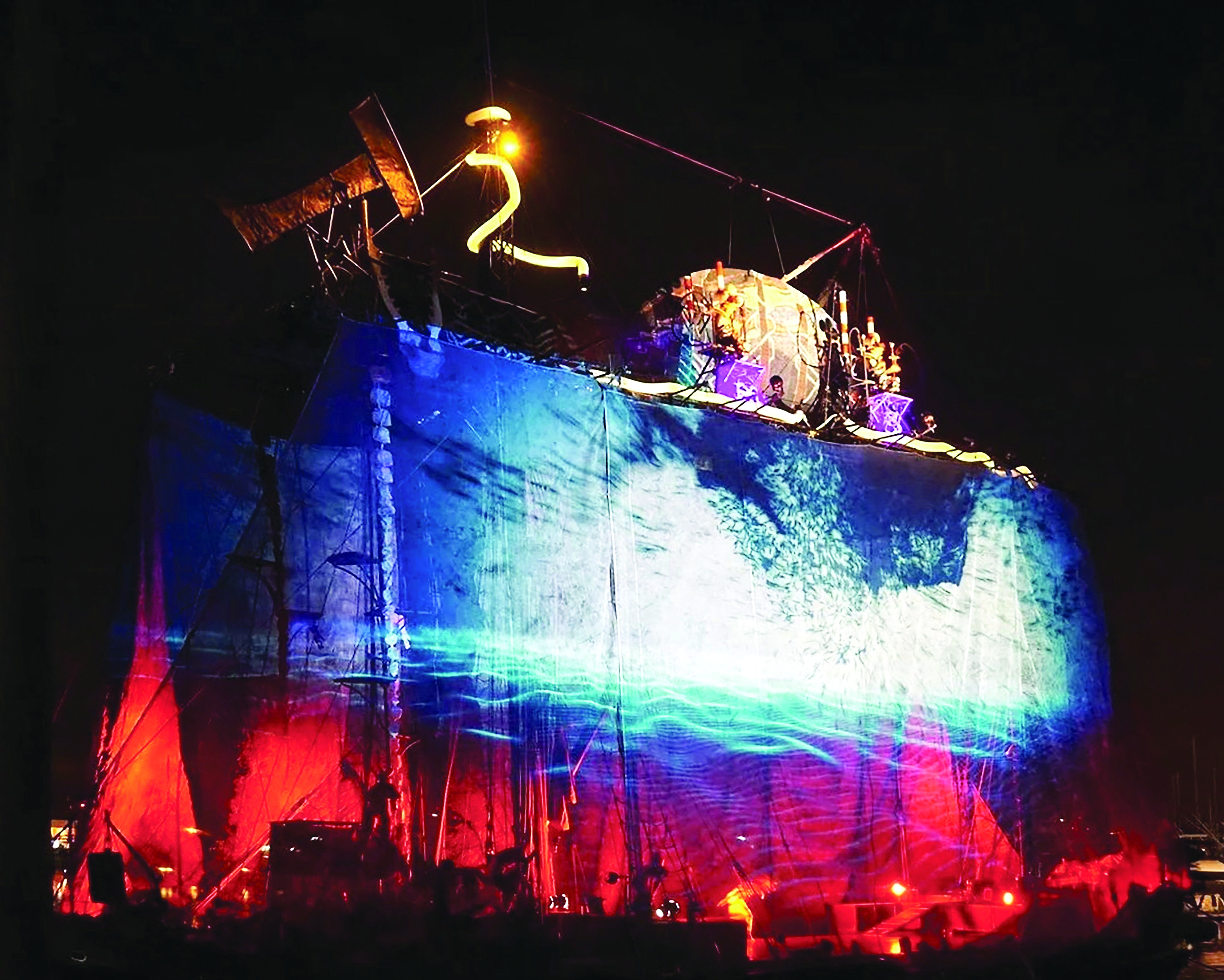 An elaborate set, featuring vibrant lighting design that features intense reds and blues.