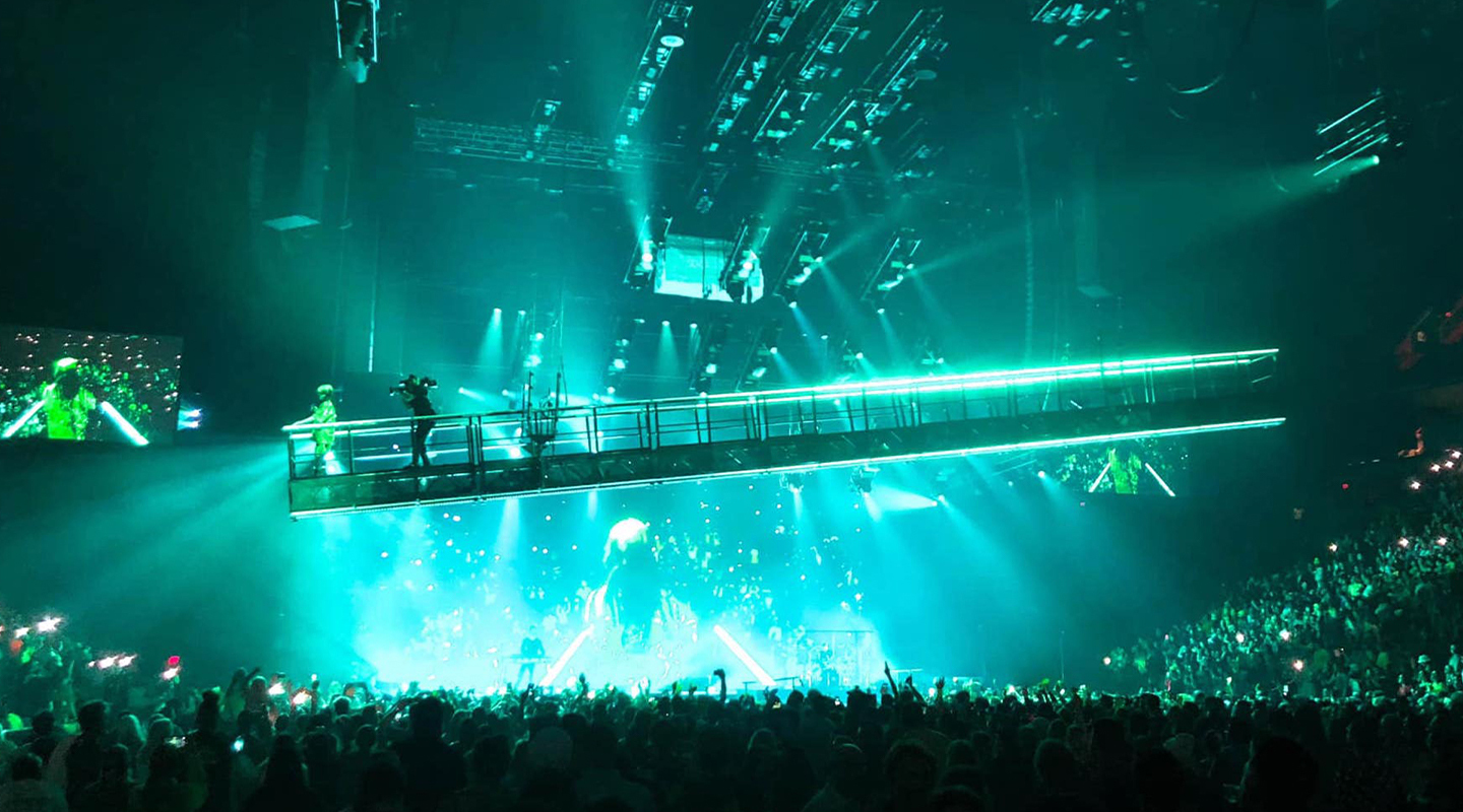 Live shot of a suspended walkway at a Billie Eilish concert.