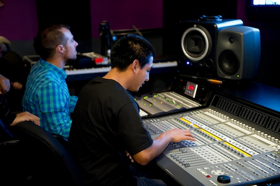 Two audio engineering students at a sound board. Photo by Pinnacle_College.